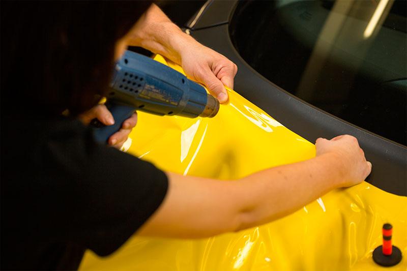 Car-wrappers-using-heat-gun-to-prepare-vinyl-foil